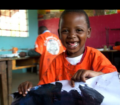 A happy student displays his art work (courtesy of Harambee Arts)